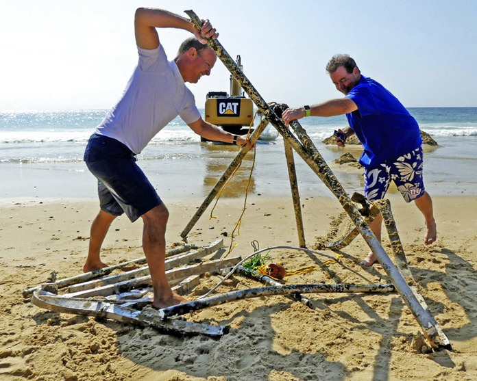 Peter Brockmann, left, president of the East Beach Association, gets help assembling pieces of a mystery object that was removed from the surf on East Beach in Westerly, R.I. (Harold Hanka/The Sun via AP)