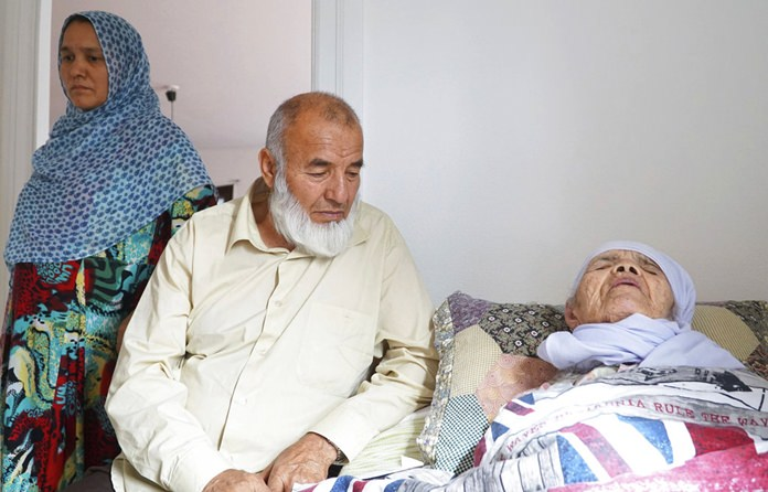 106-year-old Afghan refugee Bibihal Uzbeki rests in bed attended by her son Mohammadollah and daughter-in-law Ziba, in Hova, Sweden. (AP Photo/David Keyton)