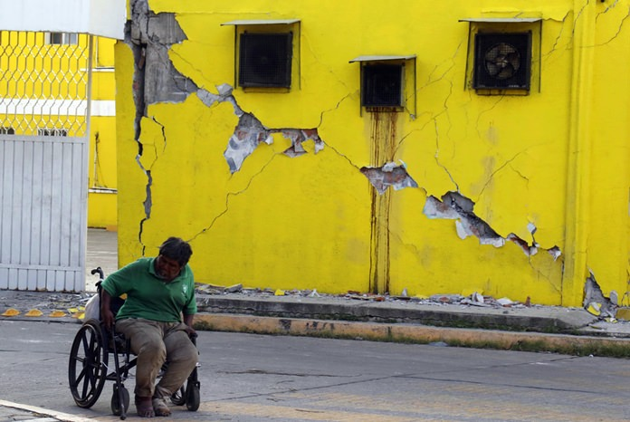 A man sits in his wheelchair backdropped by a building damaged in a massive earthquake, in Juchitan, Oaxaca state, Mexico Friday, Sept. 8, 2017.(AP Photo/Luis Alberto Cruz)