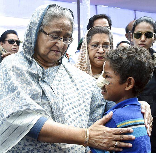 Bangladeshi Prime Minister Sheikh Hasina, center, meets with a Rohingya Muslim child at Kutupalong refugee camp, near the border town of Ukhia, Bangladesh, Tuesday, Sept. 12, 2017.(AP Photo/Saiful Kallol)
