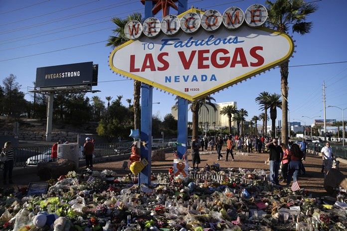 Flowers, candles and other items surround the famous Las Vegas sign at a makeshift memorial for victims of a mass shooting Monday, Oct. 9, in Las Vegas. (AP Photo/John Locher)