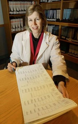 In this Dec. 12, 2002 file photo, Dr. JoAnn Manson poses with a printout from a study she directed on hormone replacement therapy for women at her office in Boston. In research results released on Tuesday, Sept. 12, 2017, Manson said hormones may be appropriate for some women when used short-term to relieve hot flashes and other bothersome menopause symptoms. (AP Photo/Elise Amendola)