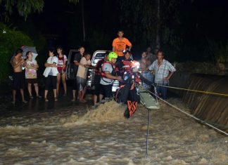 Two teams of paramedics use ropes to pull two men to shore after their SUV was swept off a river road in Khao Maikaew.