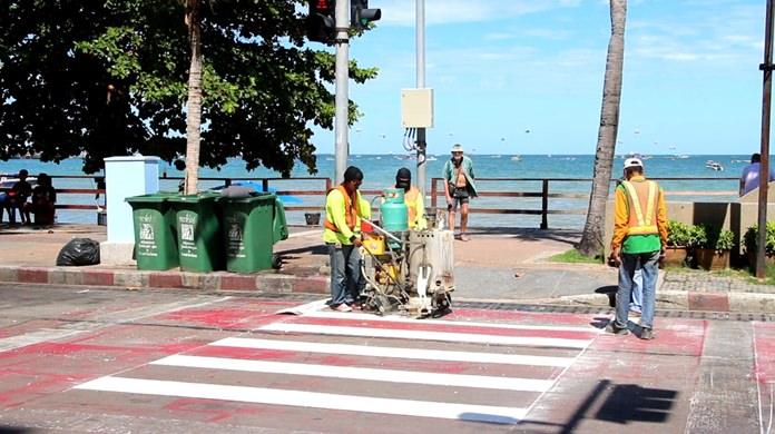 Pattaya workers repaint pedestrian crossings across Beach Road to prepare for high season.