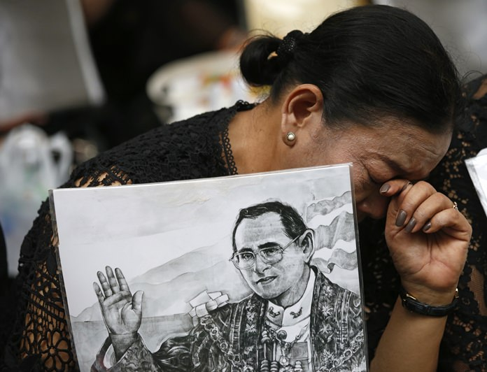 A mourner cries and holds a portrait of the late King Bhumibol Adulyadej at Siriraj Hospital where he died in Bangkok, Thailand, Friday, Oct. 13, 2017. (AP Photo/Sakchai Lalit)