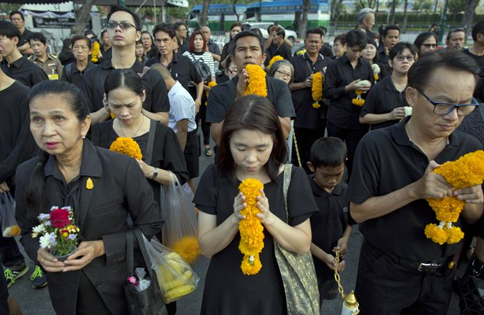 Mourners line up in front of a portrait of the late King Bhumibol Adulyadej to pay respects outside the Grand Palace in Bangkok, Thailand, Friday, Oct. 13, 2017. (AP Photo/Gemunu Amarasinghe)