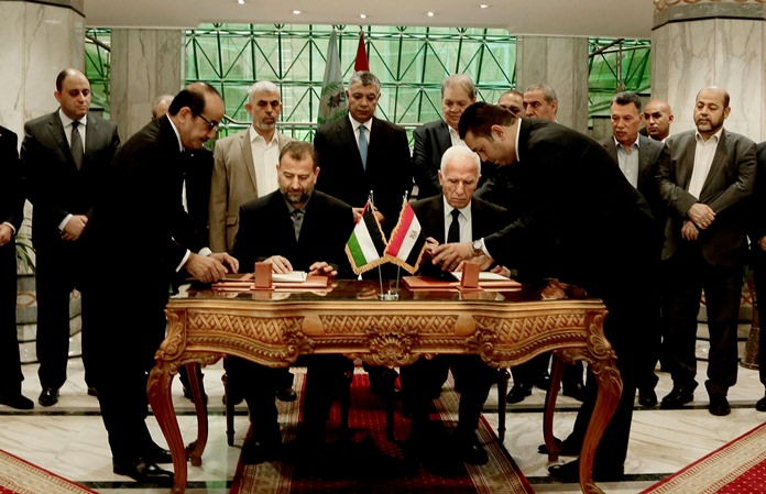 Senior Fatah official Azzam al-Ahmad, center right, and Hamas' representative, Saleh al-Arouri, center left, sign a reconciliation agreement during a press conference at the Egyptian intelligence complex in Cairo, Egypt, Thursday, Oct. 12. (AP Photo/Nariman El-Mofty)