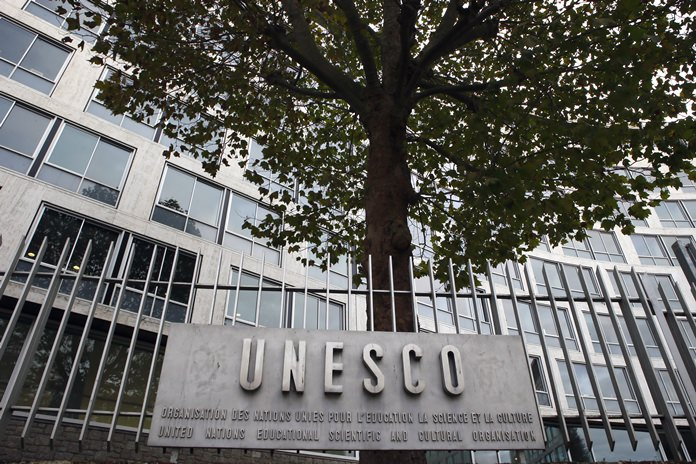 The United Nations Educational Scientific and Cultural Organization logo is pictured on the entrance at UNESCO's headquarters in Paris. (AP Photo/Francois Mori)