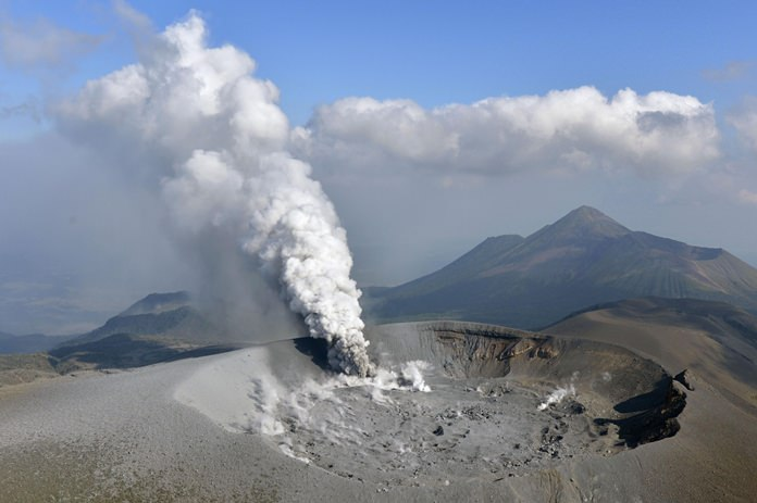 Volcanic smoke rises from the Shinmoedake volcano after its eruption in the border of Kagoshima and Miyazaki prefectures, southwestern Japan, Thursday, Oct. 12. (Tomoaki Ito/Kyodo News via AP)