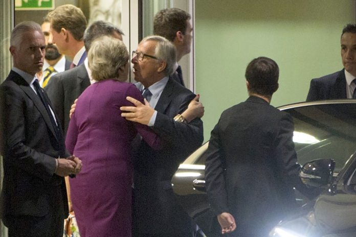 European Commission President Jean-Claude Juncker, center right, embraces British Prime Minister Theresa May, center left, after a meeting at EU headquarters in Brussels on Monday, Oct. 16. (AP Photo/Virginia Mayo)