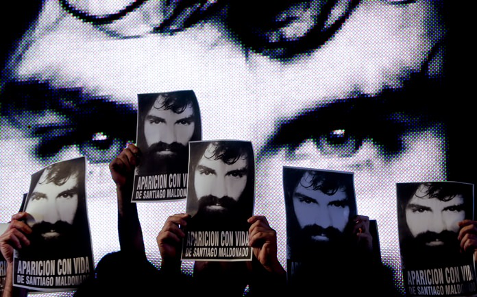 Demonstrators hold up posters of missing activist Santiago Maldonado, during a protest at Plaza de Mayo in Buenos Aires, Argentina. (AP Photo/Natacha Pisarenko)