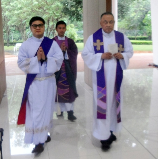 Devine Healer Fr. Corsie Legaspi (far right) enters the Assumption church.