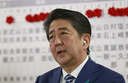 Japanese Prime Minister Shinzo Abe, leader of the Liberal Democratic Party, answers a question during a TV interview at the party headquarters in Tokyo, Sunday, Oct. 22. (AP Photo/Shizuo Kambayashi)