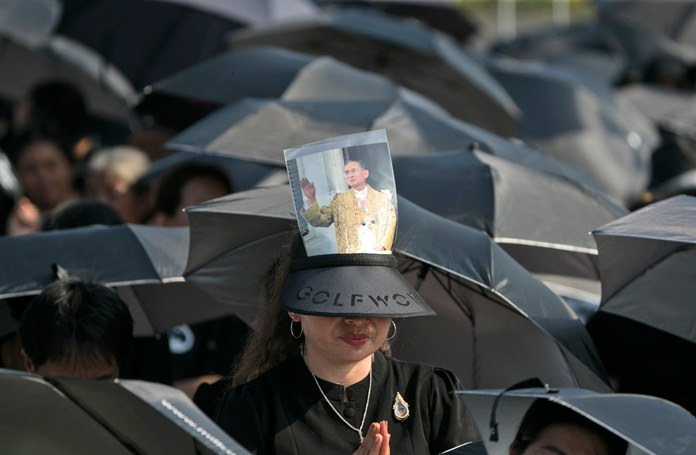 A mourner prays in a sea of black umbrellas at the funeral procession and royal cremation ceremony in Bangkok. (AP Photo/Wason Wanichakorn)