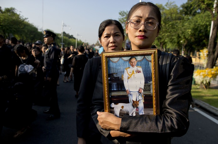 Thai mourners, carrying a portrait of HM late King Bhumibol Adulyadej gather in front of a replica of the royal crematorium in Bangkok, Thursday, Oct. 26. (AP Photo/Gemunu Amarasinghe)