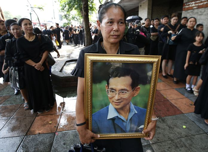 Mourners hold a portrait of late HM the late King Bhumibol Adulyadej in line to pay their respects to the Royal Urn outside the Grand Palace for last day of viewing in Bangkok, Thursday, Oct. 5, 2017. HM the late King Bhumibol Adulyadej died on Oct. 13 last year at age 88 after seven decades on the throne. The royal cremation is scheduled on Oct. 26, 2017. (AP Photo/Sakchai Lalit)