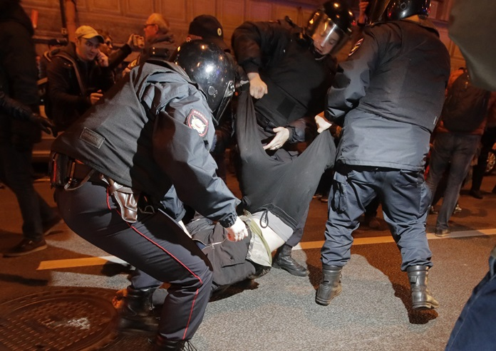 Riot police officers detain a protester during a rally in St. Petersburg, Russia, Saturday, Oct. 7. (AP Photo/Dmitri Lovetsky)