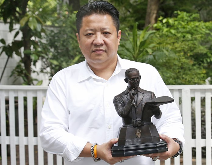 Somboon Chaisittiporn, 48, a Thai businessman, poses with a bronze statue of the late Thai King Bhumibol Adulyadej. (AP Photo/Sakchai Lalit)