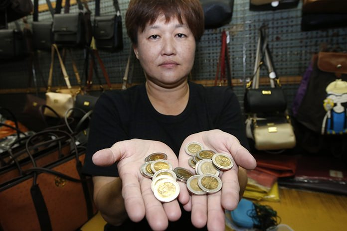 Naruemon Tananyapisut, a businesswoman, 47, shows off her collection of commemorative coins bearing the image of the late Thai King Bhumibol Adulyadej. (AP Photo/Sakchai Lalit)