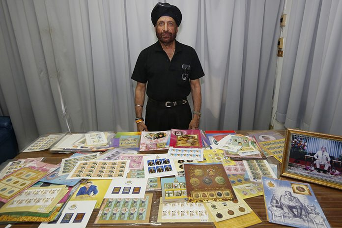 Textile manufacturer Sakda Sajjamitr, 68, stands in front of his stamp collection bearing images of late Thai King Bhumibol Adulyadej. (AP Photo/Sakchai Lalit)