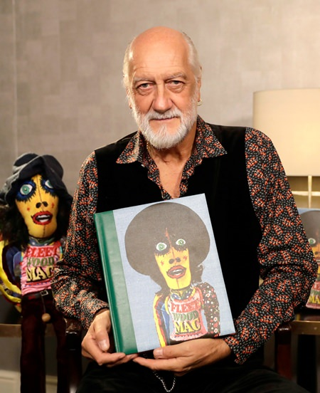 """Mick Fleetwood poses with a copy of his book """"Love That Burns - A Chronicle of Fleetwood Mac, Volume One: 1967-1974"""" during an interview in London. (AP Photo/Matt Dunham)"""