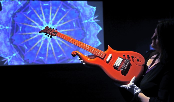 An employee shows the 'Orange Cloud Guitar' once played by artist Prince, at the 'My Name is Prince' exhibition at the O2 Arena in London, Thursday, Oct. 26. (AP Photo/Frank Augstein)