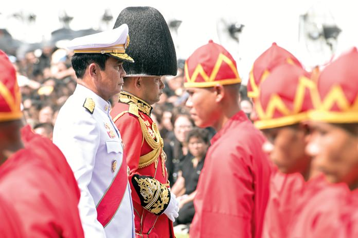 (Right) Prime Minister Prayuth Chan-ocha, left, participates at the funeral procession and royal cremation ceremony of late Thai King Bhumibol Adulyadej. (AP Photo/Kittinun Rodsupan)