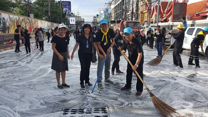 Some of the nearly 1,000 people who swept through Pattaya to clean up the city and shoreline in advance of the royal cremation ceremony, shown here cleaning South Pattaya Road in front of Wat Chaimongkol Royal Temple.