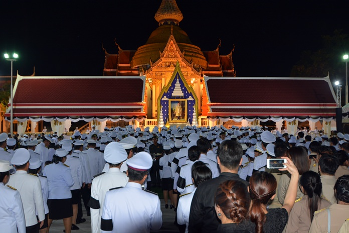 Officials in dress white uniforms and black armbands say their final goodbyes at Wat Chaimongkol.