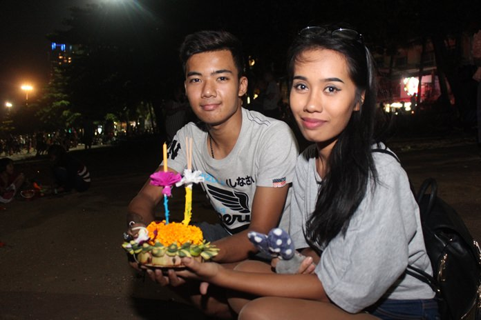 A young couple floats their krathong together, hoping for good luck.