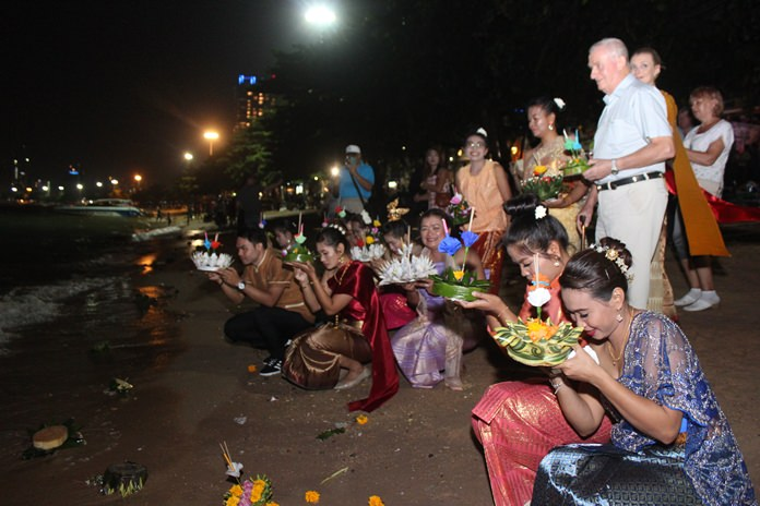 Hotel staff head to the water's edge to float their krathongs.