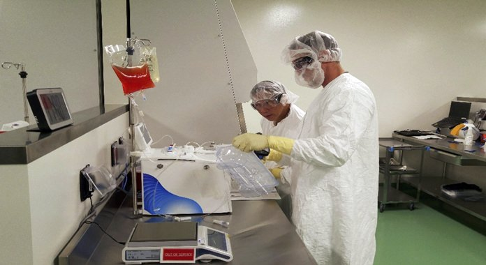 Cell therapy specialists at Kite Pharma's manufacturing facility in El Segundo, Calif., prepare blood cells from a patient to be engineered in the lab to fight cancer. (Kite Pharma via AP, File)