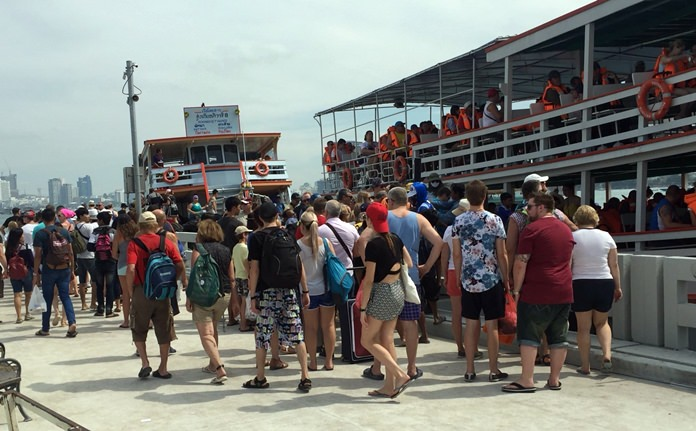Passengers are queued up all over the big concrete jetty for boats bound for Koh Larn, fishing excursions, scuba diving trips and other tourist tours.