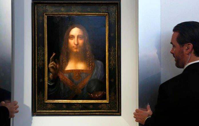 Security guards open a door to reveal Salvator Mundi by Leonardo da Vinci at Christie's in New York. (AP Photo/Seth Wenig)