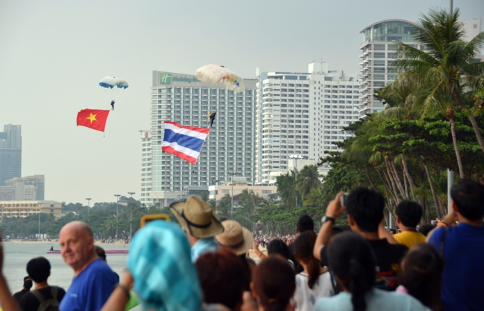 Elite jumpers parachute onto a narrow Pattaya Beach as spectators cheer them down.
