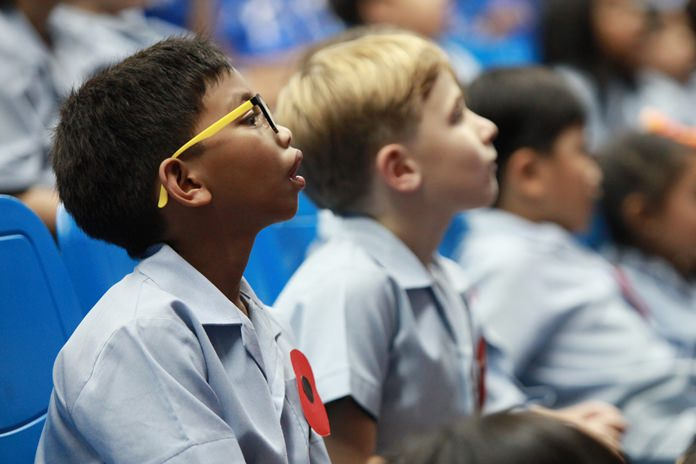 Primary students wear their poppies as they listen to the assembly.