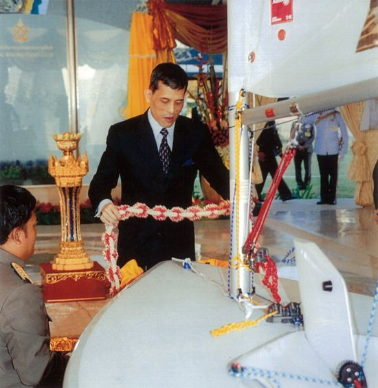 His Majesty King Maha Vajiralongkorn, then the Crown Prince, places a garland on a Laser sailing boat presented to him during the grand opening of the new Royal Varuna clubhouse in 2004.