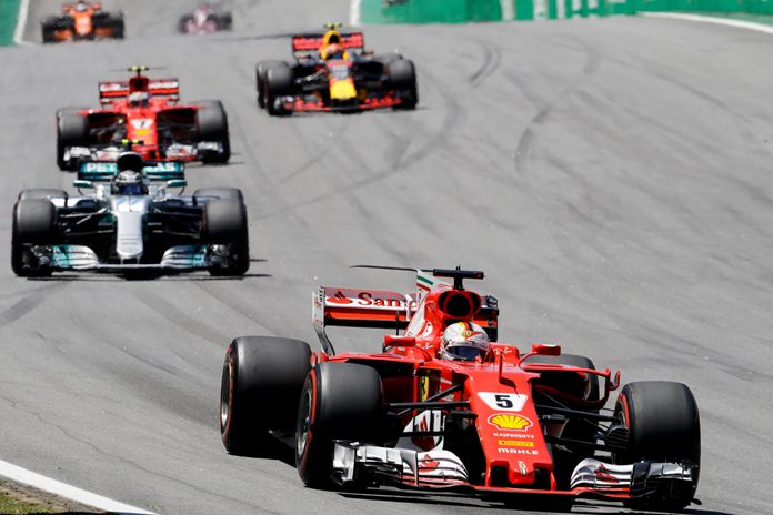 Ferrari driver Sebastian Vettel, of Germany, leads the race ahead of Mercedes Valtteri Bottas, of Finland, at the start of the Brazilian Formula One Grand Prix at the Interlagos race track in Sao Paulo, Brazil, Sunday, Nov. 12. (AP Photo/Andre Penner)