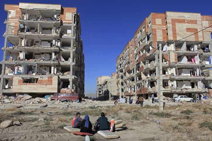Survivors sit in front of apartment buildings damaged by an earthquake in Sarpol-e-Zahab, western Iran, Monday, Nov. 13. (AP Photo/Omid Salehi)