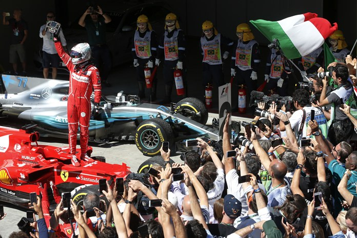 Ferrari driver Sebastian Vettel, of Germany, celebrates after winning the Brazilian Formula One Grand Prix at the Interlagos race track in Sao Paulo, Brazil, Sunday, Nov. 12. (AP Photo/Andre Penner)
