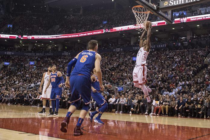 Toronto Raptors guard DeMar DeRozan (10) dunks the ball as New York Knicks forward Kristaps Porzingis (6) looks on during first-half NBA basketball game action in Toronto, Friday, Nov. 17. (Chris Young/The Canadian Press via AP)