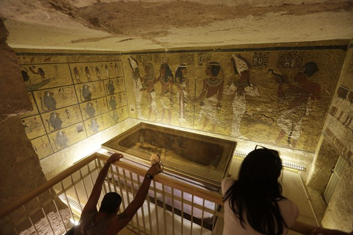 In this Thursday, Nov. 5, 2015, file photo, tourists look at the tomb of King Tut as it is displayed in a glass case at the Valley of the Kings in Luxor, Egypt. (AP Photo/Amr Nabil)
