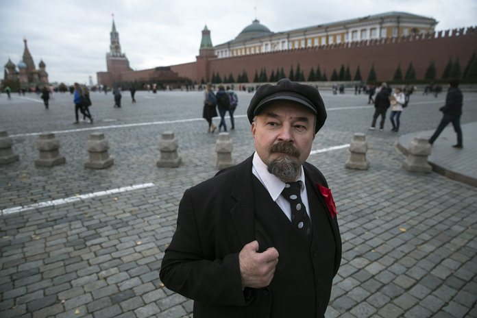 Lenin impersonator Sergei Soloviev waits for tourists in Red Square, Moscow, Russia. (AP Photo/Pavel Golovkin)