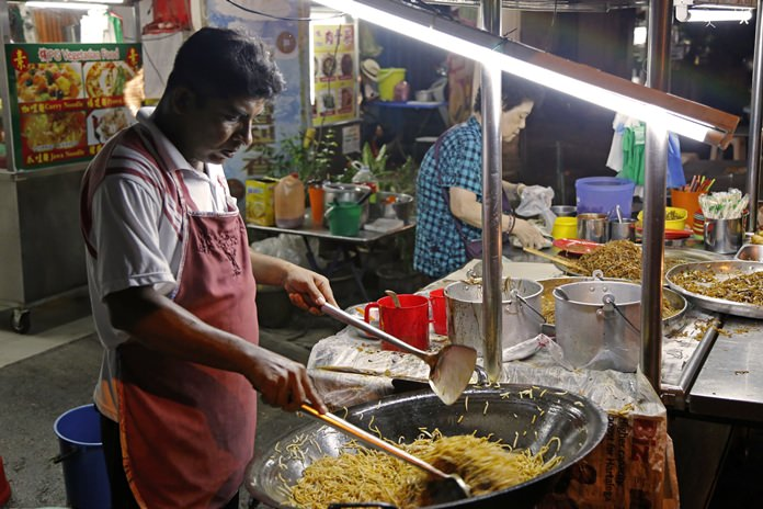 A cook stir-fries noodles at a street food stall in George Town on the island of Penang, Malaysia. (AP Photo/Adam Schreck)