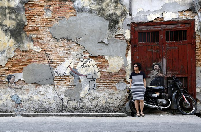 A woman leans against a motorcycle incorporated into a street art installation by artist Ernest Zacharevic in George Town. George Town oozes a hauntingly rustic charm, with colorful street art as much a draw as the historical architecture and one of Southeast Asia's tastiest street food scenes. (AP Photo/Adam Schreck)