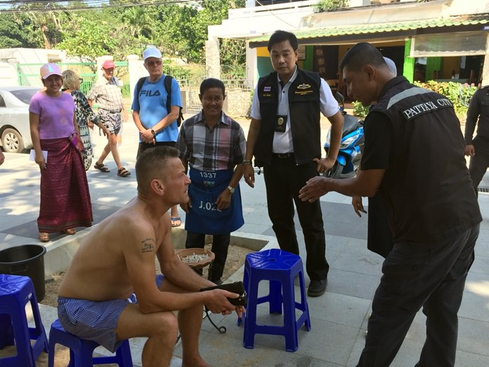 The regional director of the Marine and Coastal Resources Department, Thanet Mannoi, meets with foreign tourists in Pattaya to explain why Thailand has banned smoking on its beaches.