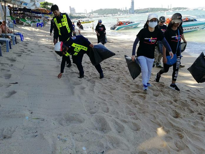 Special Task Force Law Enforcement officers and volunteers collect garbage and clean Pattaya Beach in Central Pattaya.