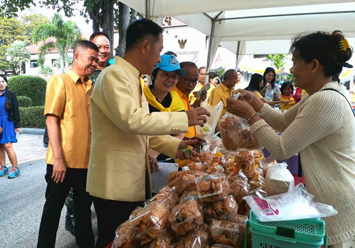 """Banglamung District Chief Naris Niramaiwong opens """"pracharat market"""" for the day, featuring 30 stalls where low-priced items were placed on sale for low-income families."""