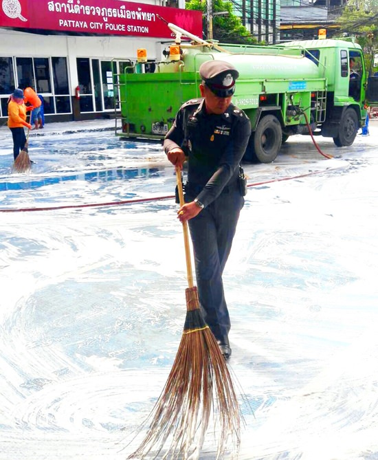 Pol. Lt. Saranpong Maithong, chief crime suppression officer leads officers in cleaning up around Pattaya Police Department.