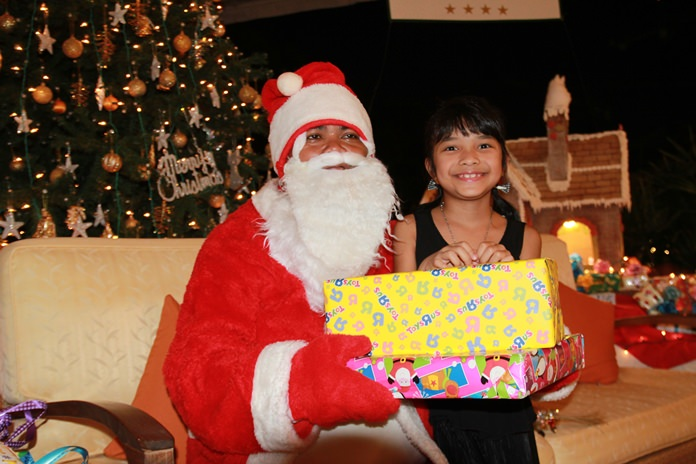 Bright eyes on this good little girl give away how delighted she is to receive a present from Santa at the Thai Garden Resort Pattaya.